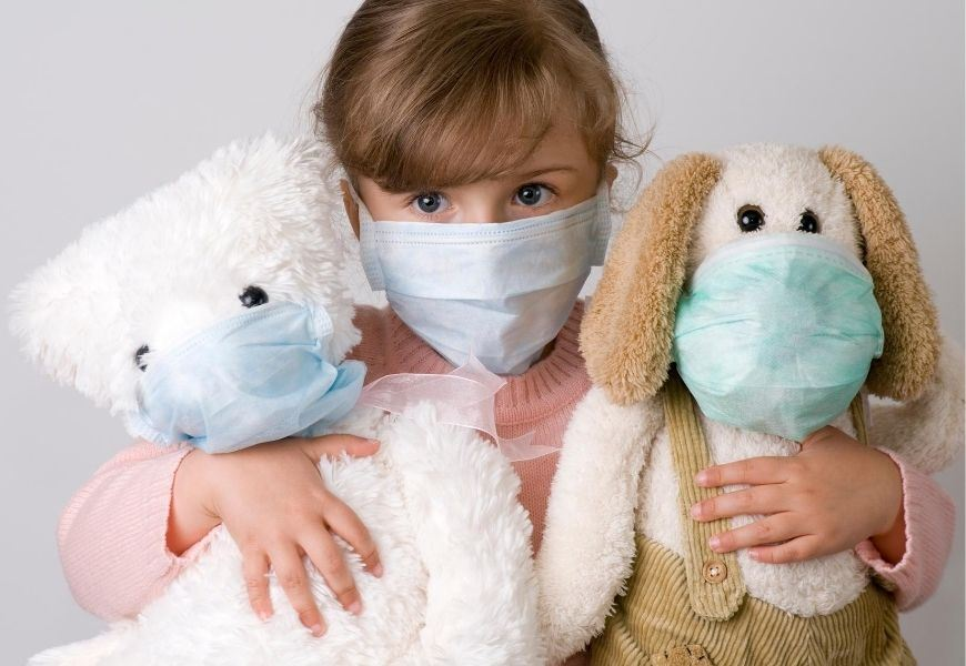 masked child with stuffed toys