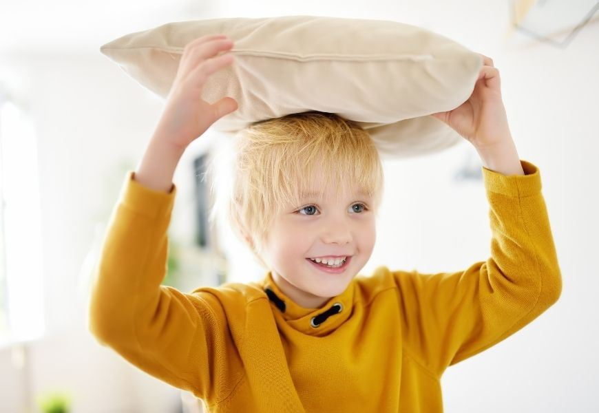 boy holding pillow on his head